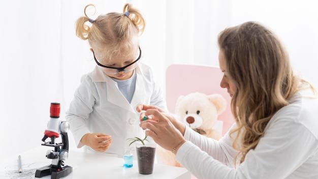 Frau, die kleinkind mit schutzbrille über wissenschaft mit mikroskop unterrichtet