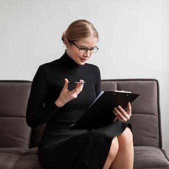 Frau, die klemmbrett betrachtet und mobile hält
