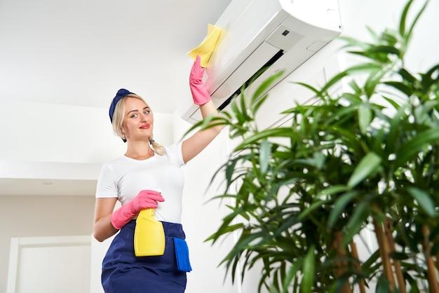 Frau, die klimaanlage mit lappen reinigt. reinigungsservice oder hausfrauenkonzept