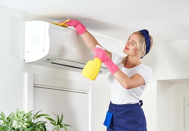 Frau, die klimaanlage mit lappen reinigt.