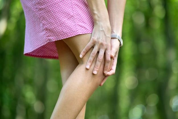 Frau, die knie mit händen hält, die starken schmerz haben.