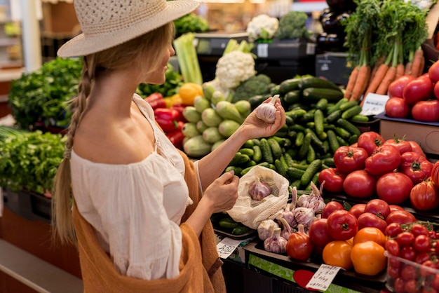 Frau, die knoblauch vom marktplatz kauft