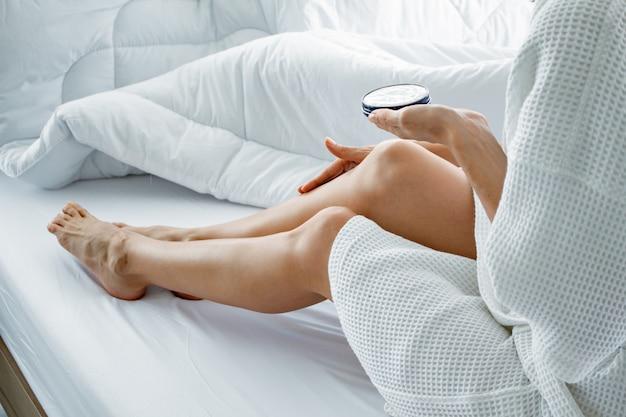 Frau, die körpercreme auf ihrem bein auf weißem bett anwendet.