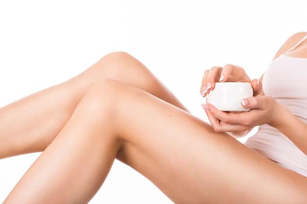 Frau, die körperlotion auf bein anwendet. hautpflegekonzept.