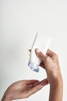 Frau, die körperpflegecreme von flasche in ihre hand mit vitiligo gießt.