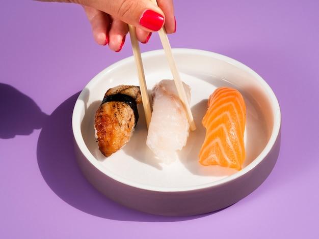 Frau, die köstliche sushi von einer platte mit sushi nimmt