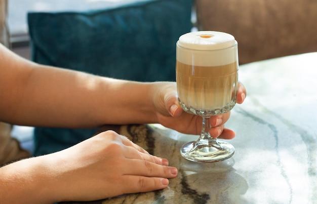 Frau, die köstlichen kaffee latte mit milchschaum trinkt