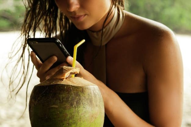 Frau, die kokosnusscocktail trinkt und smartphone verwendet