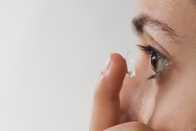 Frau, die kontaktlinse in auge