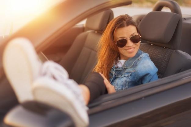 Frau, die konvertierbares auto bei sonnenuntergang genießt