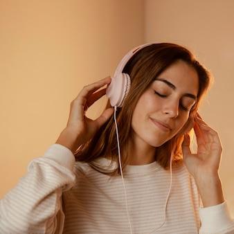 Frau, die kopfhörer für musik zu hause verwendet