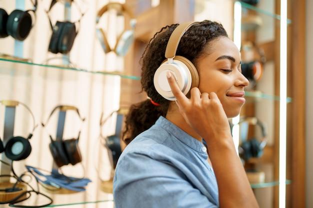Frau, die kopfhörer im akustikspeicher, rückansicht versucht. weibliche person im audio-shop, schaufenster mit kopfhörern, käufer im multimedia-shop