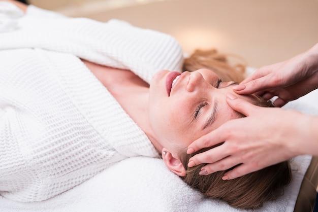 Frau, die kopfmassage am badekurort genießt