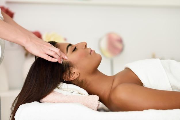Frau, die kopfmassage in der badekurort wellnessmitte empfängt.