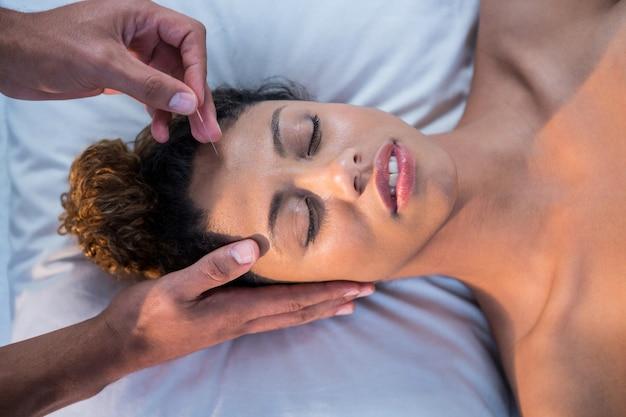 Frau, die kopfmassage vom physiotherapeuten erhält