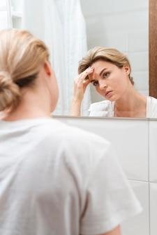 Frau, die kopfschmerzen hat und in den spiegel schaut