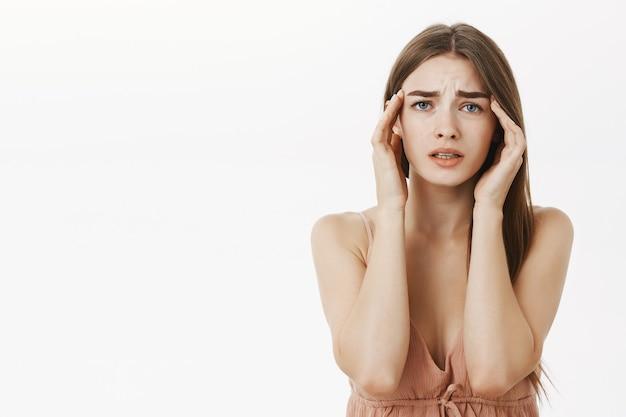 Frau, die kopfschmerzen während perioden hat, die sich frustriert fühlen und besorgt sind, schläfen zu berühren, die vor unbehagen die stirn runzeln und unter schmerzhaften gefühlen oder migräne leiden