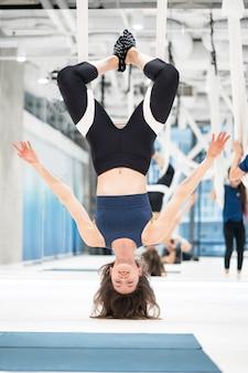 Frau, die kopfüber in einer hängematte hängt. fliegen yoga-kurs.