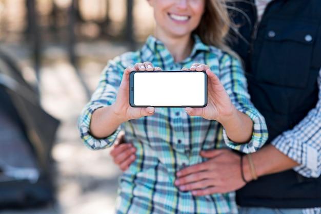 Frau, die kopierraum-mobiltelefon hält