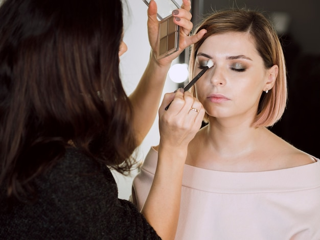 Frau, die kosmetik auf modell aufträgt