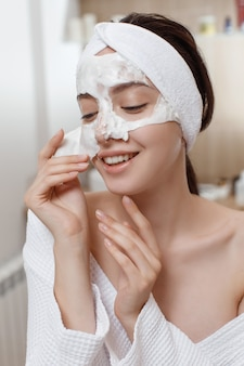 Frau, die kosmetische alginatmaske anwendet