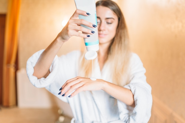 Frau, die kosmetische creme für hände, hautpflege im badezimmer anwendet. körperpflege und hygiene, gesundheitswesen, schönheitsprodukte