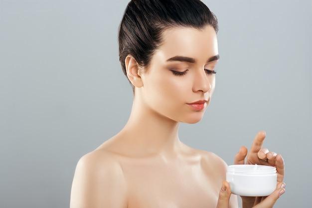 Frau, die kosmetische creme hält. schönheitsgesicht. schöne frau mit natürlichem make-up