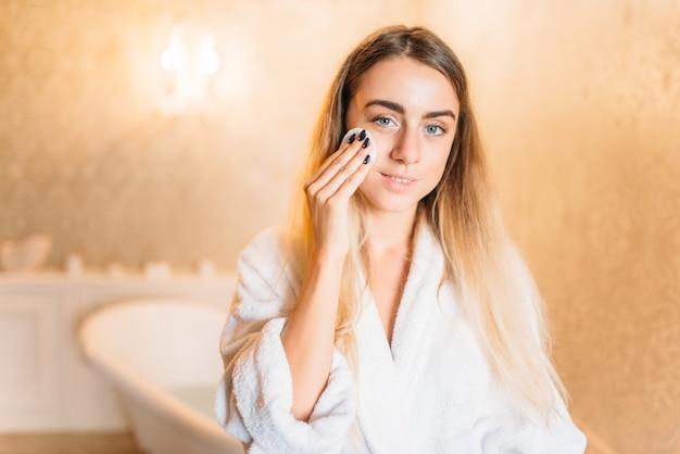 Frau, die kosmetische gesichtscreme, hautpflege im badezimmer anwendet. körperpflege und hygiene, gesundheitswesen, schönheitsprodukte