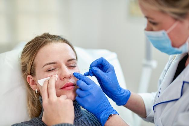 Frau, die kosmetische injektion von botox nahe den augen erhält