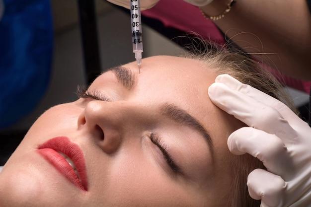 Frau, die kosmetische injektion von botulinum auf gesicht erhält. verfahren zur verjüngung und befeuchtung.