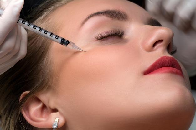 Frau, die kosmetische injektion von botulinum nahe augen erhält