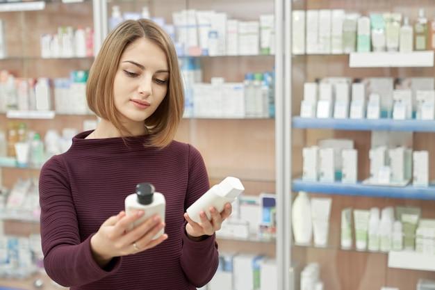 Frau, die kosmetische produkte in der apotheke wählt.