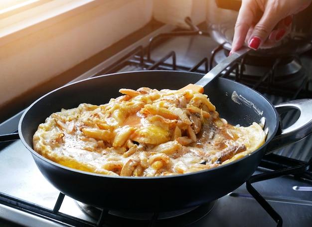 Frau, die krabbenomelett in der küche kocht.