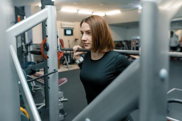 Frau, die kraftübungen mit schwergewichts- barbell tut
