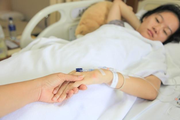 Frau, die kranke mädchenhand im krankenhaus hält