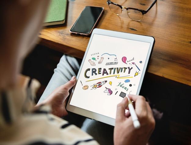 Frau, die kreative ideen auf einer tablette kritzelt