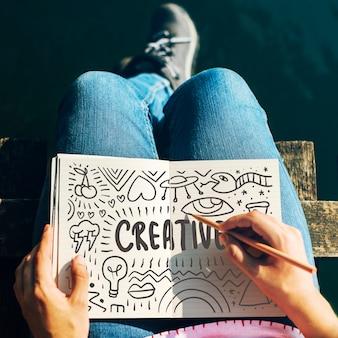 Frau, die kreative ideen in einem notizbuch zeichnet
