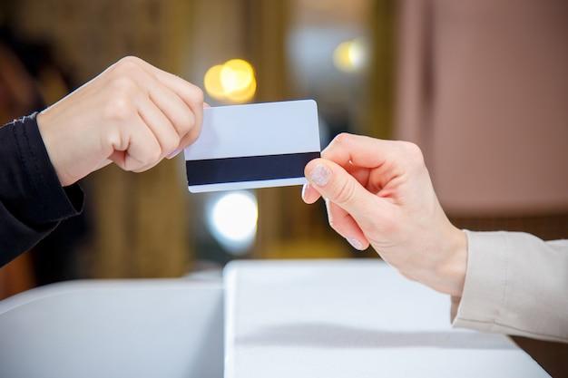 Frau, die kreditkarte an der registrierkasse überreicht