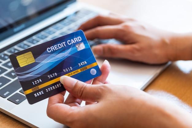 Frau, die kreditkarte auf laptop hält. online-shopping im internet mit einem laptop