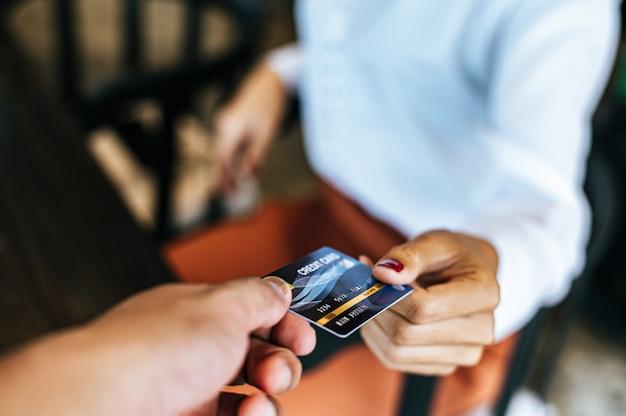 Frau, die kreditkarte einreicht, um für waren zu zahlen