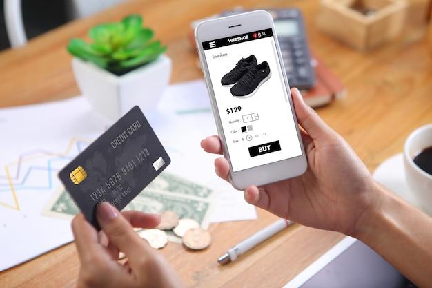 Frau, die kreditkarte für kaufschwarzlaufschuhe auf website des elektronischen geschäftsverkehrs über smartphone mit geschäftsberichtblatt und bürobriefpapier auf hölzernem schreibtisch verwendet