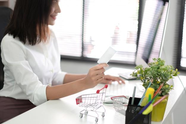 Frau, die kreditkarte hält und computer verwendet
