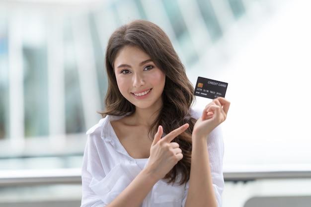 Frau, die kreditkarte hält und in der nähe des geschäfts während des einkaufsprozesses lächelt
