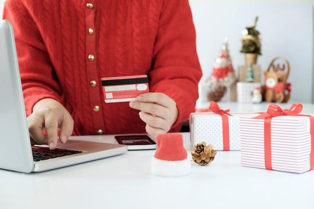 Frau, die kreditkarte hält und online kauft macht.