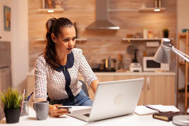 Frau, die kreditkarte in der heimischen küche verwendet, um online-zahlung zu tätigen. kreative dame, die online-transaktionen mit einem digitalen notizbuch durchführt, das mit dem internet verbunden ist.