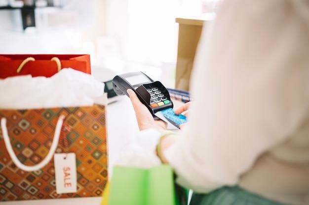 Frau, die kreditkarte in zahlungsterminal einsetzt