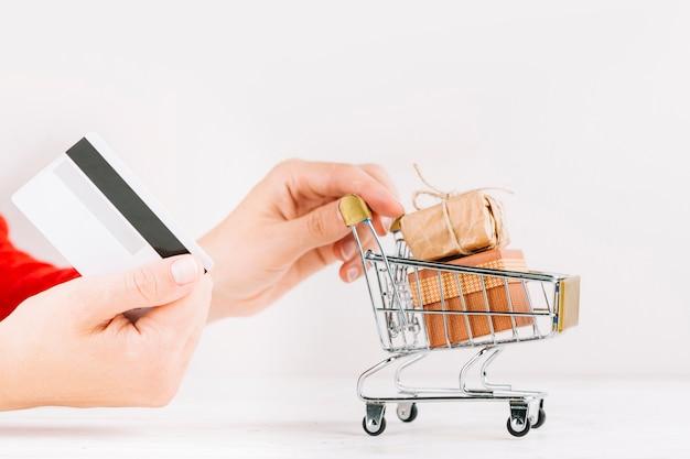 Frau, die kreditkarte und kleinen lebensmittelgeschäftwarenkorb mit geschenkboxen hält