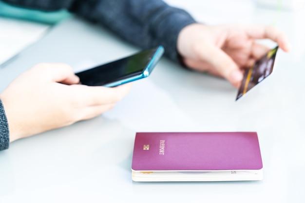 Frau, die kreditkarte und reisepass mit smartphone für online-einkauf auf deck i hält
