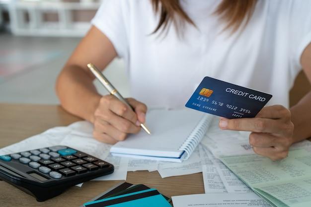 Frau, die kreditkarte und schreiben, konto und sparkonzept hält.