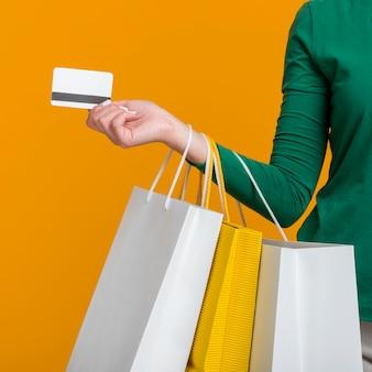 Frau, die kreditkarte und viele einkaufstaschen hält